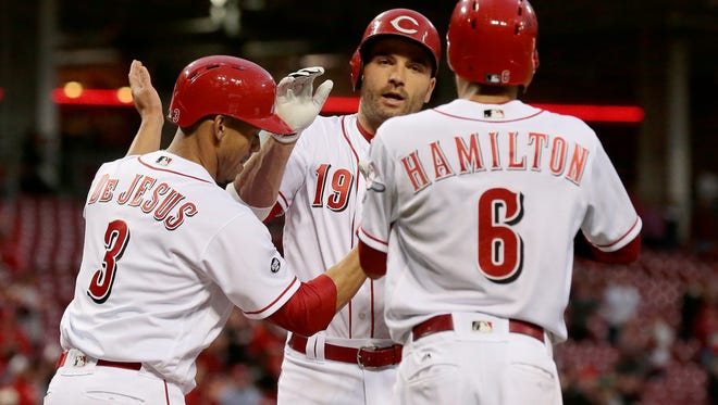 Cincinnati Reds first baseman Joey Votto (19) high-fives with second baseman Ivan De Jesus Jr. (3) and center fielder Billy Hamilton (6) at home plate after his three-run home run in the bottom of the third inning of the MLB National League game between the Cincinnati Reds and the San Francisco Giants at Great American Ball Park in downtown Cincinnati on Monday, May 2, 2016. The Reds led 6-3 after scoring six runs in the bottom of the third inning.