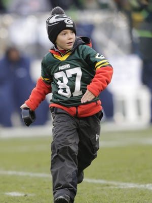 Austin Beauchamp, 6, of De Pere runs off the turf at Lambeau Field after retrieving the kicking tee as the Shopko Kick-off Kid following the opening kickoff of the Green Bay Packers' 38-10 win over the Seahawks.