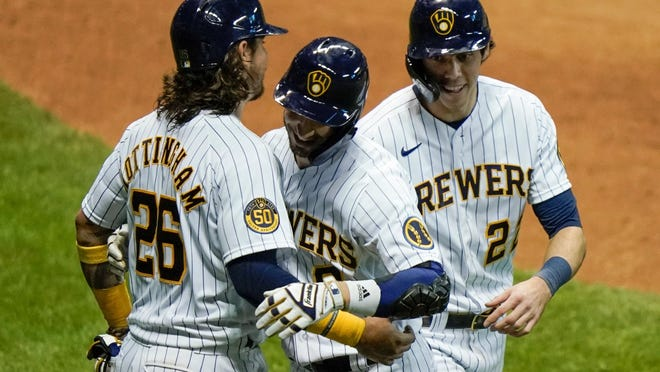 The Milwaukee Brewers' Ryan Braun, center, celebrates his three-run home run with Jacob Nottingham (26) and Christian Yelich during the eighth inning against the Kansas City Royals on Saturday in Milwaukee.