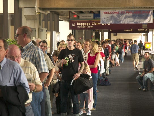 Passengers await a security check at Philadelphia Airport.