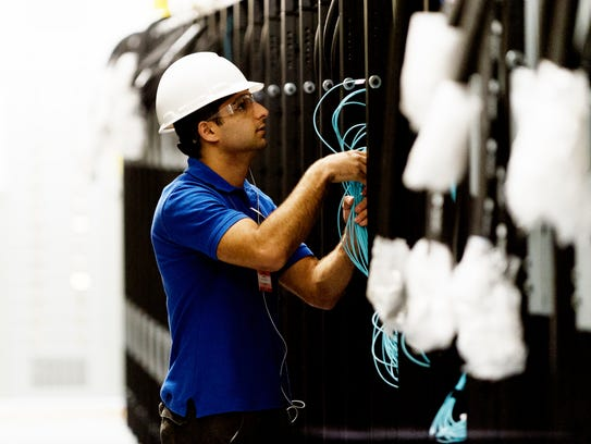 A worker installs the fiber-optic cable within the