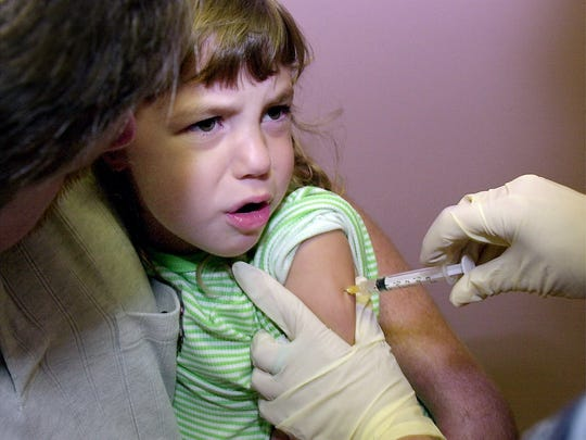 Hayley Van Dusen of Florence, Kentucky gets a measles and mumps immunization shot at Boone County Health Clinic in Florence in 2012.