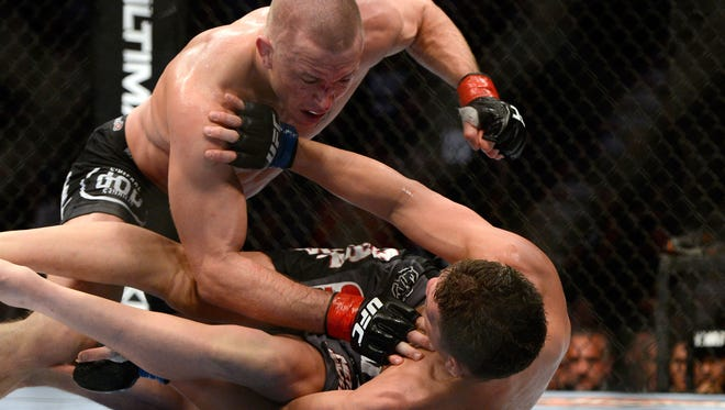 Georges St.Pierre (top) throws punches at Nick Diaz during their Welterweight title bout at UFC 158 at Montreal's Bell Centre.