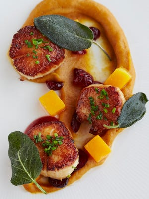 Seared sea scallops with butternut squash confit, pickled cranberry puree and fried sage at Restaurant Nicholas in Middletown.