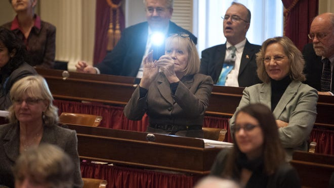 Rep. Jean O'Sullivan, center, takes a photo from her desk on the opening day of the Legislature.