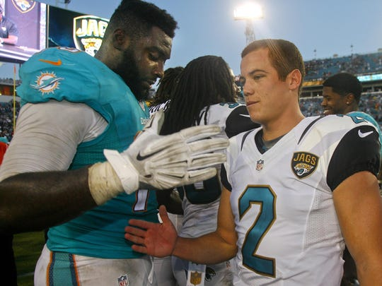 Marist College alumni Terrence Fede of the Miami Dolphins, left, and Jason Myers of the Jacksonville Jaguars, meet on the field after the Jaguars defeated the Dolphins 23-20 on Sept. 20, 2015 in Jacksonville, Florida.