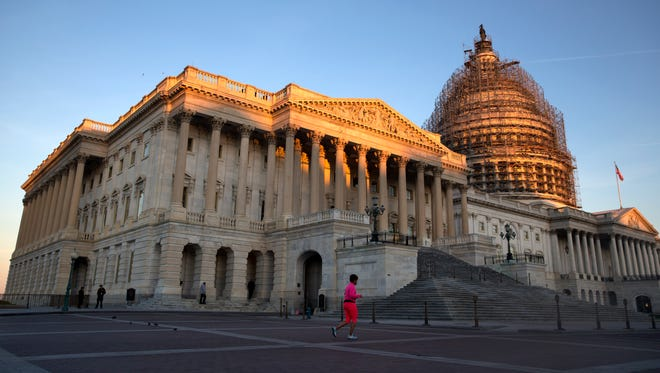 A jogger runs past the House side of the Capitol at sunrise on Capitol Hill in Washington on Oct. 22.