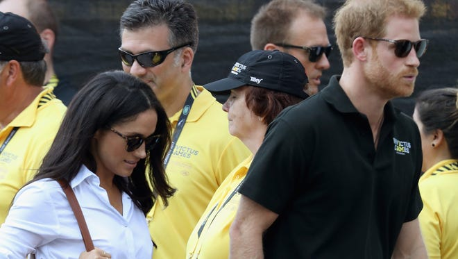 Prince Harry and girlfriend Meghan Markle hold hands as they arrive for wheelchair tennis match at Invictus Games in Toronto, Sept. 25, 2017.