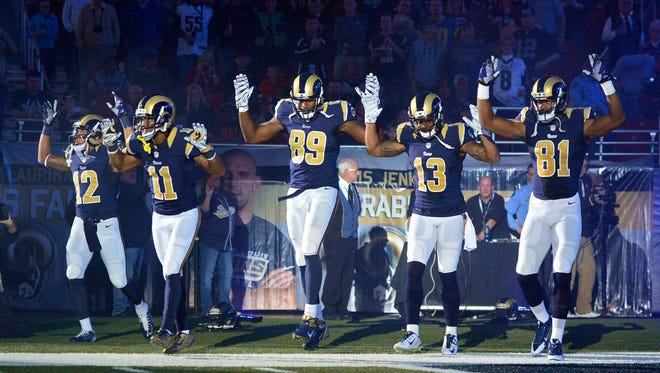 St. Louis Rams wide receiver Stedman Bailey (12), wide receiver Tavon Austin (11), tight end Jared Cook (89), wide receiver Chris Givens (13) and wide receiver Kenny Britt (81) put their hands up to show support for Ferguson protesters before a game against the Oakland Raiders in St. Louis Nov. 30, 2014.