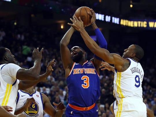 New York Knicks forward Tim Hardaway Jr. (3) is fouled by Golden State Warriors' Andre Iguodala during the first half of an NBA basketball game Tuesday, Jan. 23, 2018, in Oakland, Calif. (AP Photo/Ben Margot)