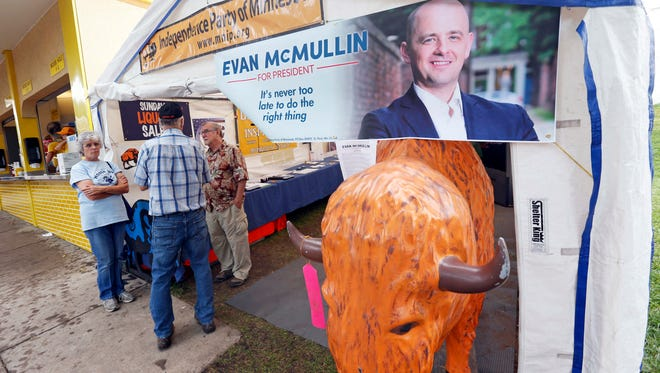 """Fair goers check out Minnesota's Independence Party tent Tuesday, Aug. 30, 2016, at the Minnesota State Fair in Falcon Heights, Minn. The party is hoping to hitch a ride on the """"Never Trump"""" movement back to glory as a major party. Evan McMullin, the face of Republicans opposed to Donald Trump, will represent Minnesota's Independence Party on the ballot. (AP Photo/Jim Mone)"""
