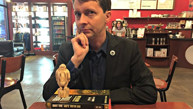 "Lars Pearson of Des Moines is owner of Mad Norwegian Press, a publishing company that specializes in science fiction titles. Pearson is shown with a stack of his company's books and a wooden carving of a Yeti, a villain from ""Doctor Who."""