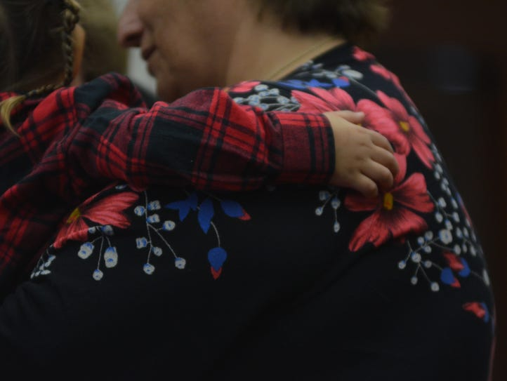 A child hugs his new mother at the adoption ceremony