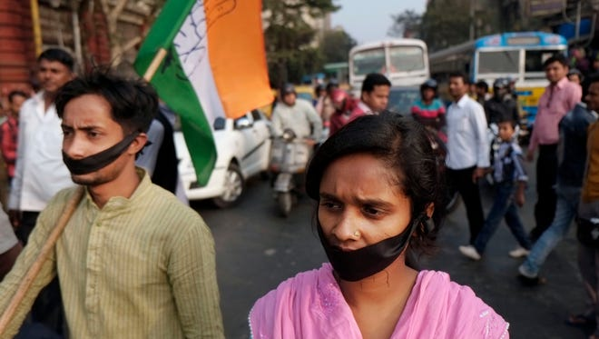 Activists of Indian National Congress with black bands around their mouth block traffic during a protest against a gang-rape and murder of a 16-year-old girl at Madhyamgram, about 16 miles north of Kolkata, India, on Jan. 3, 2014.