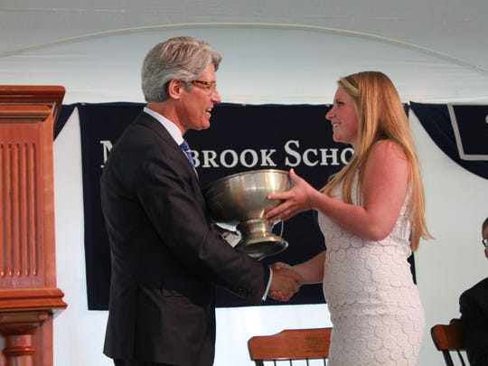 Millbrook School Headmaster Drew Casertano on Sunday gives the Community Service Cup Award to Mansell Ambrose for her involvement with campus life and community service.