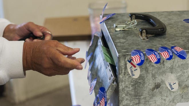 Linda Olson turns in her ballot at the Montana ExpoPark Exhibition Hall Tuesday, September 15, 2015.