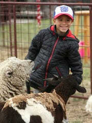 Noriel Casiano, 8, feeds animals at the petting zoo during Saturday's Texas Independence Day celebration.