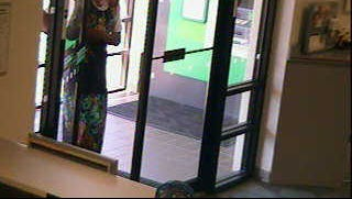 A suspected male bank robber -- wearing a wig and dress -- enters the M & T Bank on Haines Road in Springettsbury Township on Wednesday.