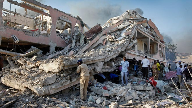 Somalis gather and search for survivors by destroyed buildings at the scene of a blast in Mogadishu, Somalia, Oct. 14, 2017.