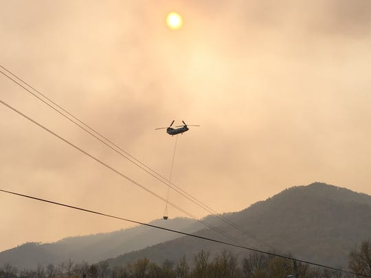 A helicopter, contracted by the U.S. Forest Service, carries water from the French Broad River to dump on the Neddy Mountain fire.
