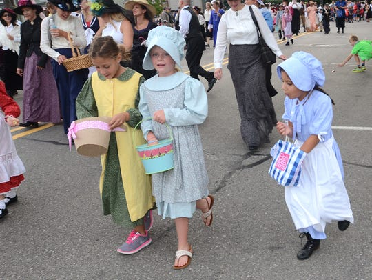 Young ladies in appropriate Victorian-era garb march