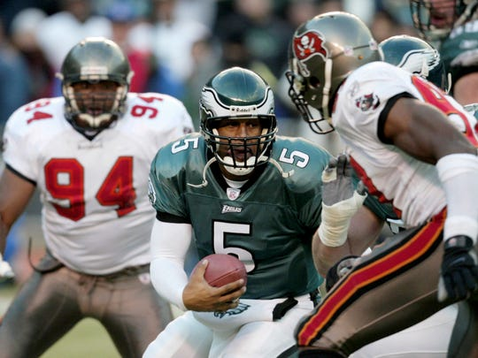 Philadelphia Eagles quarterback Donovan McNabb (5) challenges the defense of Tampa Bay Buccaneers' Simeon Rice, right, and  Greg Spires (94) during the NFC Championship game at Veterans Stadium in Philadelphia, Sunday, Jan. 19, 2003.