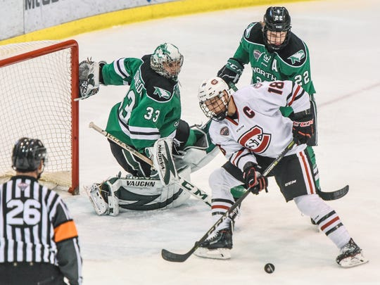 St. Cloud State's Judd Peterson works with the pick in front of North Dakota goaltender Cam Jonnson and Rhett Gardner during the first period of the Saturday, Dec. 9, game at the Herb Brooks National Hockey Center in St. Cloud.