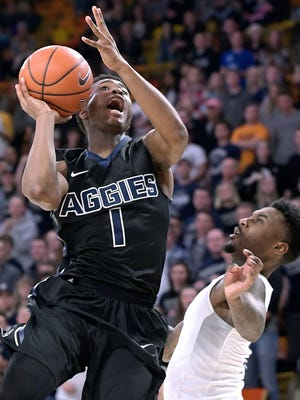 Utah State guard Koby McEwen drives to the basket as Nevada guard Marcus Marshall defends him during their game Wednesday.