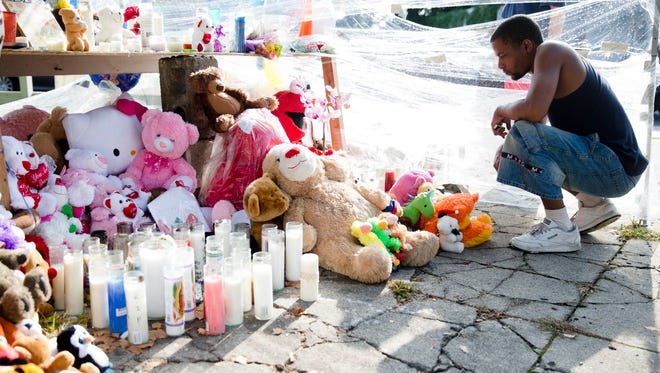 Richard Starchia pays his respects Monday, July 28, 2014, at a makeshift memorial for three children who were killed Friday by a hijacked car that lost control and hit a group of people in Philadelphia. Two men have been charged in the case.