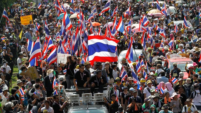 epa03967173 Thai anti-government protesters march on a main street during a massive rally heading to occupy the Government Complex in Bangkok, Thailand, 27 November 2013. Thousands of protesters led by Suthep Thaugsuban marched in Bangkok street to occupying the main government ministerial complex in an effort to paralyze the government and force reforms to Thailand's political system.  EPA/RUNGROJ YONGRIT ORG XMIT: RUN568