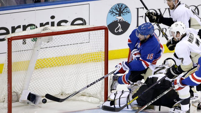 Rangers center Derick Brassard, left, pokes the puck into the open net with Penguins goalie Marc-Andre Fleury out of position in the second period Sunday night.