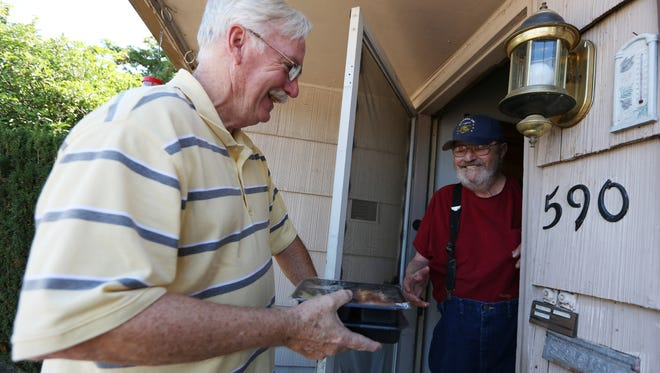 Gary Grombacher, left, who volunteers twice a week for Marion-Polk Food Share Meals on Wheels, makes a delivery to Marvin Reese's home on Friday, Aug. 12, 2016, in Salem.
