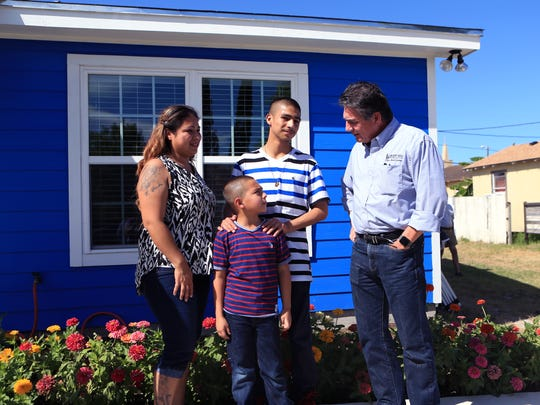 Toni Alaniz (from left) and her sons, Alonso Garcia, 7, and Tony Angel Alaniz, 14, talk with Andy Saenz, regional manager for public relations for Flint Hills Resources, before the start of the Habitat for Humanity key ceremony in which the family received the keys to their home on Wednesday, July 19, 2017. Flint Hills Resources and the Coastal Bend Community Foundation each provided grants in the amount of $25,000 to fund the building of the home, which the family will pay back over the course of a loan.