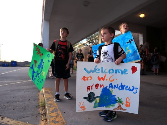 Andrews Elementary School students and brothers Levi Landery, 9 (from left) and Ryan Landery, 5, greet students from Aransas County Rockport-Fulton Independent School District who have registered in their school in Portland on Tuesday, Sept. 5, 2017. Aransas County has indefinitely closed their district after sustaining damage from Hurricane Harvey. As of Friday, over 500 students from the district had registered at the Gregory-Portland Independent School District.