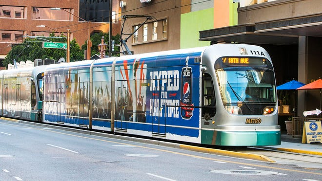 A light-rail train heads north on Central Avenue just north of Adams Street in downtown Phoenix. The Valley's light-rail system receives funding from the Proposition 400 transit tax.