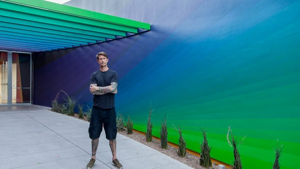 """James """"Dalek"""" Marshall posing with one of his murals"""