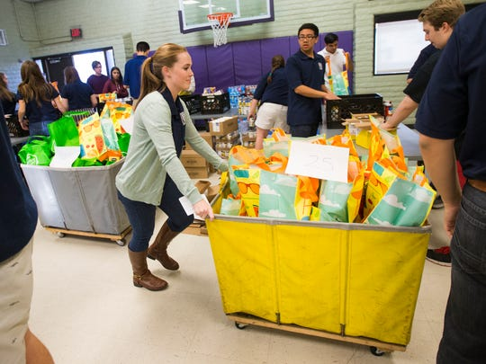 Kelsey Yurek (center), 17, pushes a cart while working with other members of the Scottsdale Mayor's Youth Council to package ingredients for over 300 Thanksgiving meals at Vista del Camino in Scottsdale on Nov. 17, 2014.
