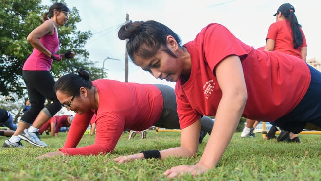 Recruit Gennie-May Whitt, right, performs plank push-ups during Pacific Daily News' 2017 Bridal Boot Camp at Gov. Joseph Flores Beach Park in Tumon on Jan. 4, 2017.