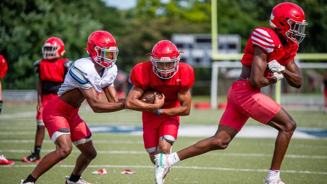 Van Horn senior quarterback Sean Mitchell, left, works on handoffs to running back Lamonte Belshe, center, during a recent practice.