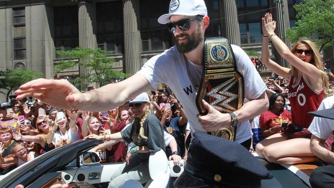 The Cavaliers' Kevin Love shakes hands with fans along Euclid Avenue during the team's NBA Championship celebration in 2016.