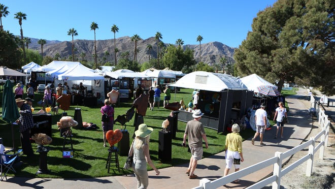 People walk the perimeter of Rancho Mirage Community Park during the Rancho Mirage Affaire in Rancho Mirage on Saturday.