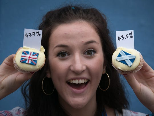 Cuckoo's Bakery waitress Pippa Perriam holds up the result of the cupcakes referendum that the bakery has been holding since March 7 by selling Yes, No and undecided cupcakes at Cuckoo's Bakery in Dundas Street, on September 17 in Edinburgh, Scotland.