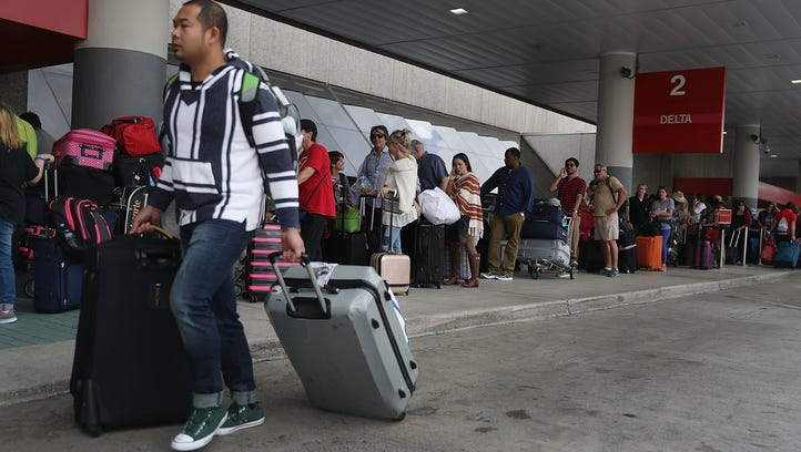 Passengers queue up at Fort Lauderdale Hollywood International Airport Saturday morning after the airport reopened following Friday's deadly shooting.