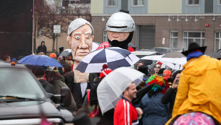 Revelers wear busts of Michigan Governor Rick Snyder and the fictional character RoboCop before the start of the 8th Annual Marche du Nain Rouge parade.
