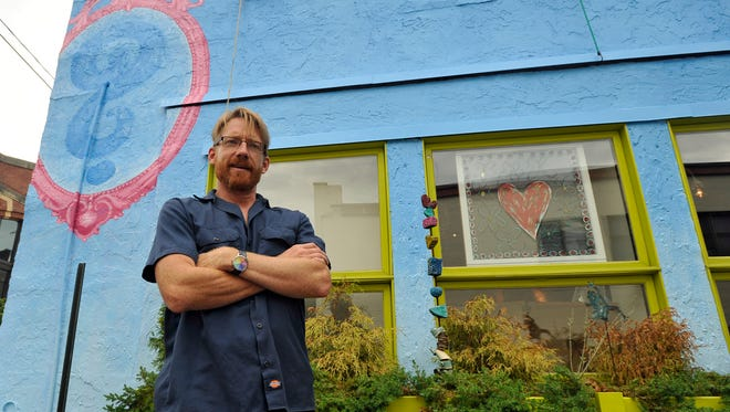 Artist and owner of Renovate with Color, Scott David Smith, stands in front of the beginnings of a mural on the side of Willow's Dream on Broadway in downtown Asheville.