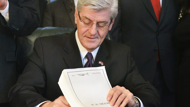 Gov. Phil Bryant makes House Bill 585 official Monday during a signing ceremony at the state Capitol in Jackson. The bipartisan criminal justice reform package is designed to protect public safety, clarify sentencing practices and control corrections costs.