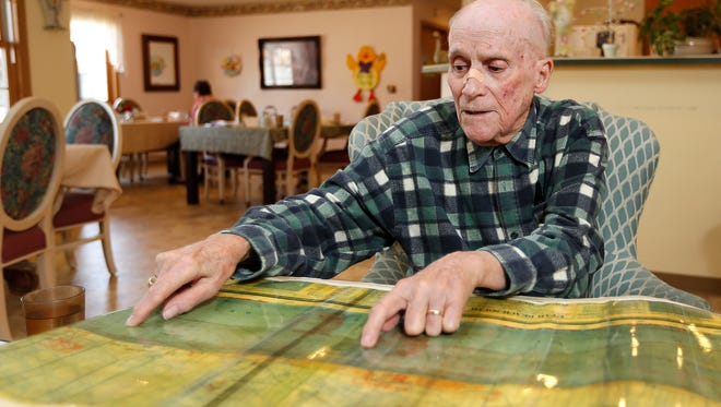 Ed Gilleran looks at a replica of a map that identified where the Germans had placed coastal defenses. Gilleran was told to destroy the map, but instead he held onto it. He donated the original to the National World War II Museum in New Orleans at the urging of renowned historian Stephen Ambrose, whom he met in 1989.