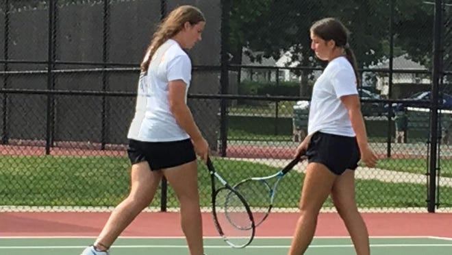 Topeka High No. 1 doubles players Adisyn Caryl, left, and Haley Carpenter touch rackets after a point in Wednesday's Topeka High Invitational. Caryl and Carpenter went 4-0 to win the No. 1 doubles title.