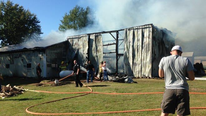 Firefighters work to put out a barn fire in Delaware County on Monday.
