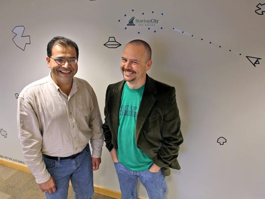Tej Dhawan, left, and Christian Renaud, right, stand in front of a mural depicting the video game Asteriods at  the one-year anniversary party for StartupCity Des Moines.
